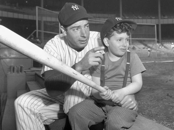 Joe DiMaggio of the Yankees passes on a few batting tips to his five-and-a-half-year old son, Joseph III, prior to the Yankees — Washington Senators game at Yankee Stadium, New York, April 27, 1947.
