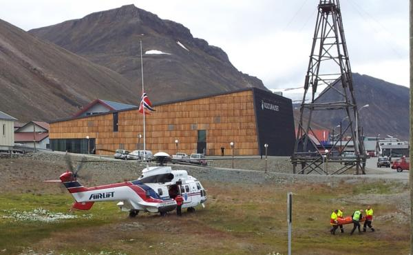 An injured person is carried from a helicopter in Longyearbyen after a polar bear killed one person and left four other members of a British group seriously injured.