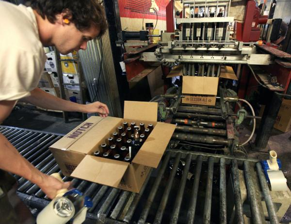 "Cellarman Cooper Reid packs cases of beer at the Ipswich Ale Brewery in July. New rules put out by the state's alcohol commission require ""farmer-brewers"" like Ipswich to grow 50 percent of their own grains and hops, or get it from domestic farms."