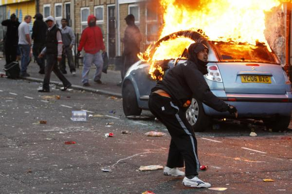 A rioter throws a rock at riot police in Clarence Road in Hackney, London, Monday. Rioting and looting continued into the night Monday in parts of London, as well as in Birmingham. The unrest was prompted by the initial rioting in Tottenham and then in Brixton on Sunday night.