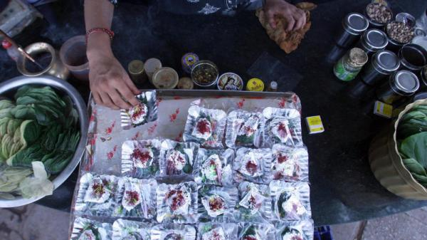 In India, the centuries-old tradition of chewing betel leaves, or <em>paan</em>, spread with spices and sweeteners is losing popularity. In this file photo from 2006, an Indian shopkeeper arranges silver foils of <em>paan </em>at his roadside shop in New Delhi.
