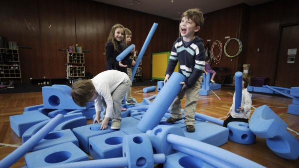 Children  play with blue foam building blocks at the Blue School  in New York City  on March 31. The Blue School is one of many competitive private preschools in  Manhattan, founded by original members of the Blue Man Group so they could send  their own children to a school that they felt supported creative offerings for  their children.