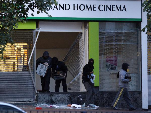 Youths steal electrical goods from a store in Birmingham, central England, on August 9. While the riots started after a man was shot to death by police in north London, their actual cause continues to be debated.