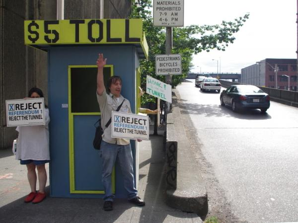 Volunteers with Protect Seattle Now set up a mock toll booth at a downtown  entrance to the Alaskan Way Viaduct, to remind drivers that they'll have to pay  to use the planned tunnel.