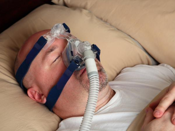 A man with sleep apnea wears a CPAP machine mask in bed.