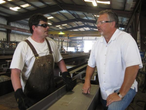 Precision Ironworks President Steve Leighton, right, says government regulations are keeping his company from growing.