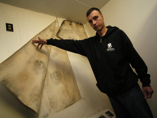Jeremy Duncan, a wounded Army specialist assigned to Walter Reed's Building 18, peels back the wallpaper in one of its rooms to show mold in January 2007.