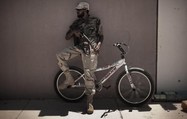 A Libyan rebel fighter leans on a bicycle as he patrols the empty streets of  the residential area of the port of Brega Monday. The city represents the eastern front of the rebels' attempt to isolate Moammar Gadhafi in Tripoli.