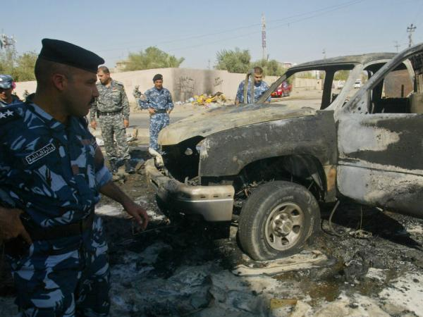 Iraqi security forces inspect damages at the site of an explosion in the northern city of Kirkuk on Aug. 15. Across Iraq, more than 40 separate attacks killed nearly 90 people on this day.