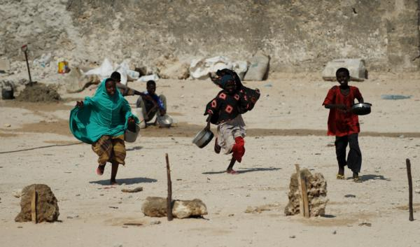 Children run toward workers distributing hot meals in Mogadishu Thursday. Some 12 million people in parts of Ethiopia, Djibouti, Kenya, Uganda and Somalia are at risk of starvation in the wake of the region's worst drought in decades.