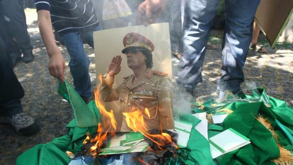 Protesters burn a portrait of Libyan leader Moammar Gadhafi and copies of his Green Book outside the Libyan Embassy in Ankara. Turkey, on Monday, Aug. 22, 2011. Libyan rebels taken many parts of the Libyan capital Tripoli as they try to oust Gadhafi.