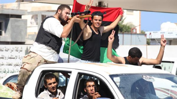 Rebel fighters drive through western Tripoli, Libya, on Monday. Large numbers of rebels have entered the capital, but Moammar Gadhafi's loyalists are putting up stiff resistance.