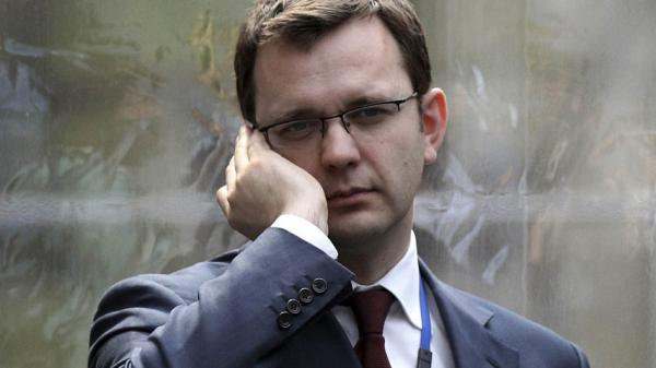 Andy Coulson, formerly editor of the tabloid News of the World, and later David Cameron's director of communications, speaks on a mobile phone in London on April 13, 2010. London police arrested Andy Coulson on July 8 in relation to Britain's tabloid phone-hacking scandal.
