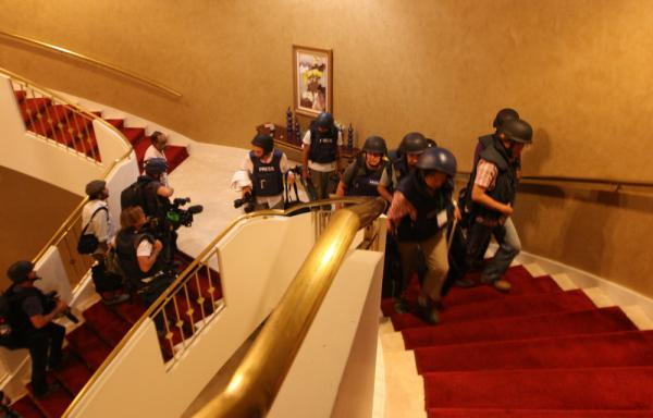 Foreign journalists in protective gear climb the stairs at the Rixos hotel where they were confined, as rebel forces overran Gadhafi's Bab al-Azizya headquarters in Tripoli.