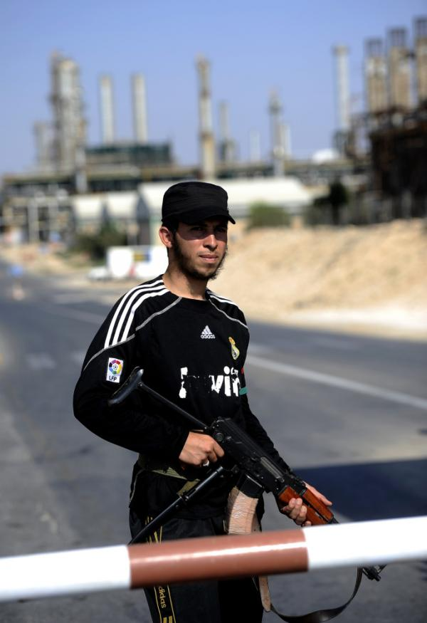 A Libyan rebel stands guard at the entrance to the Zawiya oil refinery, about 30 miles west of Tripoli, on Aug. 19. Libyan rebels taken complete control of the key oil refinery. Before the conflict, Libya supplied 2 percent of the world's oil, but restarting oil field operations won't be a simple task.