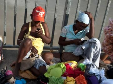 Two women check their cell phones as they hawk their wares on a bridge over the Artibonite river, whose waters are  believed to be the source of Haiti's 2010 cholera outbreak.