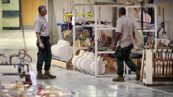 Federal Investigators look through the workshop at the Gibson Guitar factory during a raid on the facility in Memphis on August 24th.