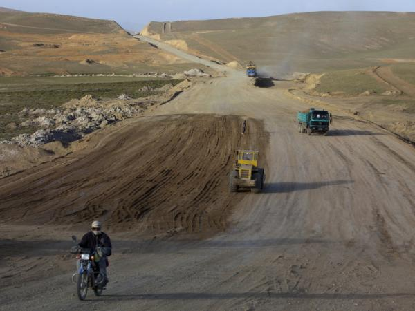 An Afghan man rides a motorcycle along the still under construction Bamiyan-Yakawlang road in Yakawlang, Afghanistan, June 10, 2011. Despite the construction of new roads, many of them are unsafe to drive.