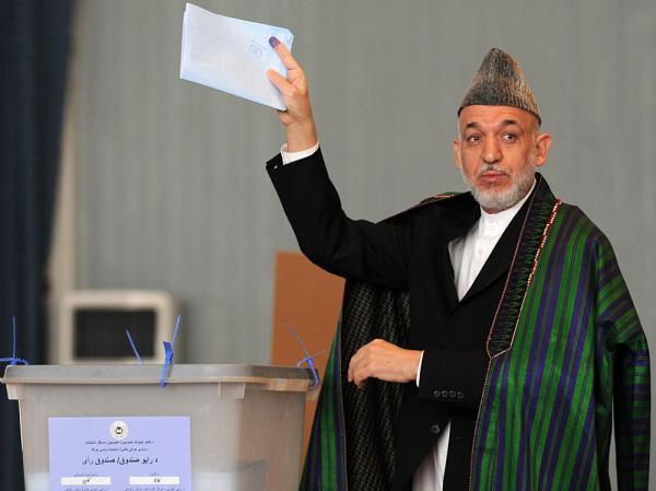 Afghan President Hamid Karzai gestures before casting his vote at a polling station in Kabul, September 18, 2010, in parliamentary elections that were marred by allegations of fraud.