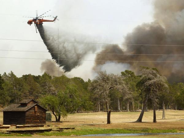 Firefighting helicopters dump water and flame retardant after loading up with water from a pond at Lost Pines Golf Club as they fight a fire in Bastrop State Park on September 6, 2011 in Bastrop, Texas.