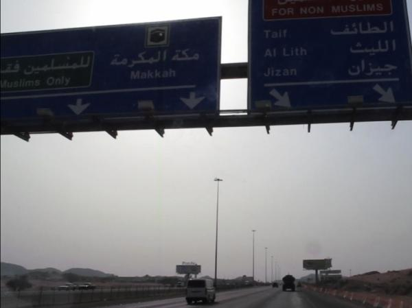 Signs above Highway 15 indicate two routes to Mecca, Islam's holiest  city: one for Muslims and one for non-Muslims.