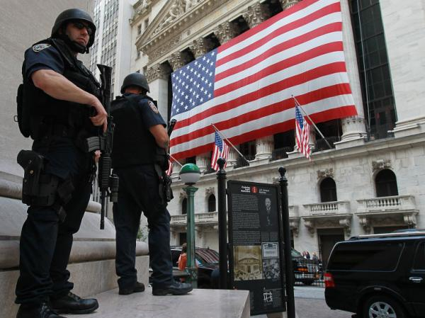 New York City policemen stand guard near the New York Stock Exchange on Friday. Security in New York and Washington have been stepped up based on what the government is calling a credible but unconfirmed threat of a possible car bomb attack.