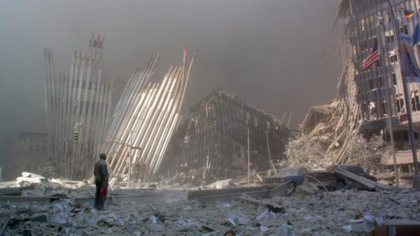 A man standing in rubble shouts to see if anyone needs help after the collapse of the first World Trade Center Tower in New York on Sept. 11, 2001.