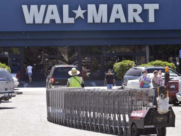 In virtually every county, there is a  Walmart open every hour of every day and  every one of those Walmarts  is being visited by 37,000 people a week —  that's 220 people an hour,  in every Walmart every hour of  the day. Here a Walmart worker pulls carts at a store in Pittsburg, Calif. on June 20.
