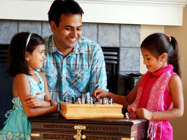 Naresh Dhiman plays chess with his two daughters. Dhiman's wife encouraged him to launch his own company, and she now works 3 to 4 hours a day overseeing their software developers in India.