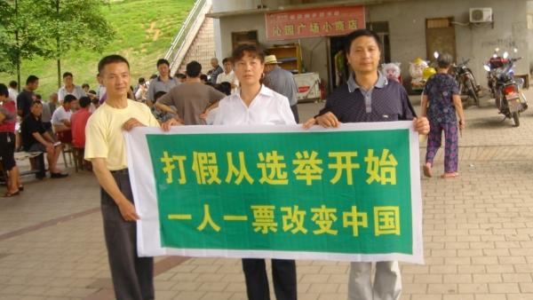 "Labor activist Liu Ping (center) has unleashed a wave of candidates in the latest round of local elections. Here, she and two other campaigners hold a banner that declares, ""Fighting fake  [things] should start with elections. One person, one vote will change  China."""