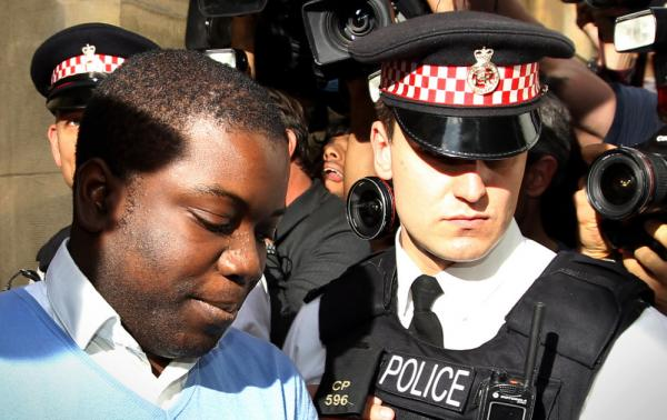 UBS equities trader Kweku Adoboli (L) is led into a prison van as he leaves City of London Magistrates Court in central London on Friday.