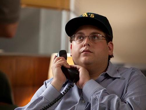 Jonah Hill takes on a surprisingly more serious role than his previous work as Peter Brand, an overachieving Ivy League geek who likes to crank statistics on everyone.
