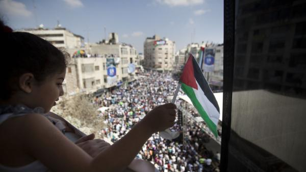 A Palestinian girl waves a flag during a demonstration in support the Palestinian bid for recognition of statehood at the U.N. on Sept. 21 in Ramallah, West Bank. Palestinian President Mahmoud Abbas is expected to submit a letter to the U.N. Security Council to petition for statehood during the U.N. General Assembly.