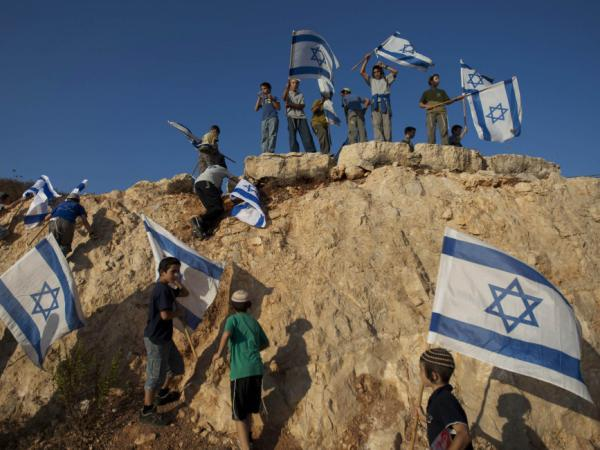 Israeli settler youths wave Israeli flags at the start of a protest march against Palestinian statehood, from the West Bank Jewish settlement of Itamar, Sept. 20.