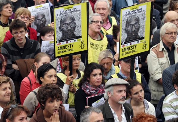 People hold placards of rights group Amnesty International during a demonstration in Paris on Wednesday.