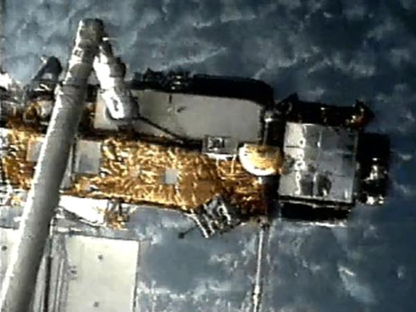 A screen grab from NASA shows UARS attached to the robotic arm of the space shuttle Discovery in 1991 as it was deployed.