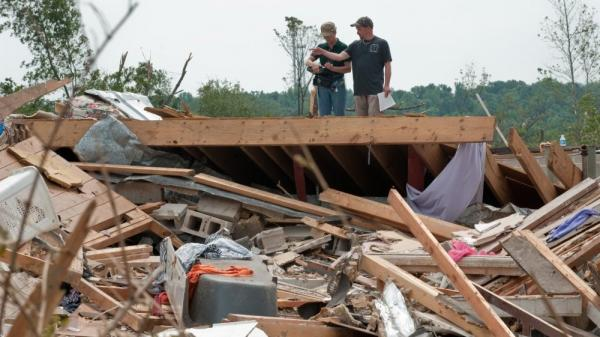 A resident speaks to a Federal Emergency Management Agency agent atop his destroyed house in the devastated town of Hueytown, Ala., on May 1. FEMA will run out of money to help disaster victims by early next week unless Congress acts.