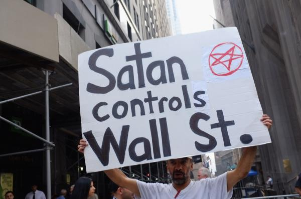 "A demonstrator holds up a sign in front of the  New York Stock Exchange in New York City. Hundreds of activists affiliated with the ""Occupy Wall Street"" demonstrations have begun living in a park in the Financial District near Wall Street."