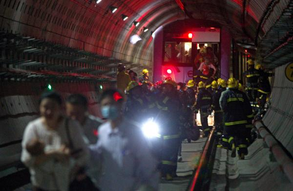 Rescue workers evacuated passengers after a subway train crashed into another train between stations Tuesday in Shanghai.