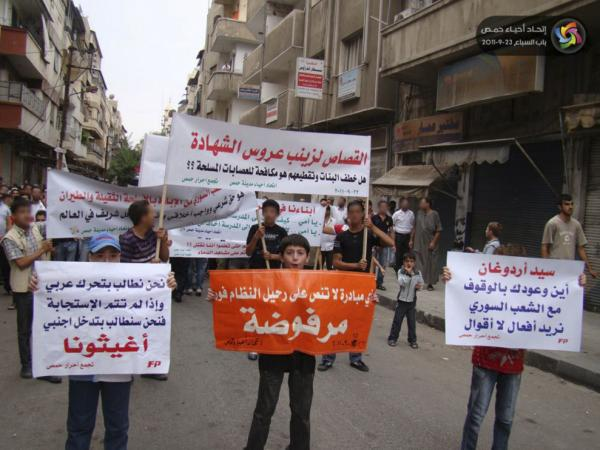 Syrian protesters hold up placards demanding intervention from other Arab countries during a demonstration against the Syrian regime in the central province of Homs on Sept. 23.