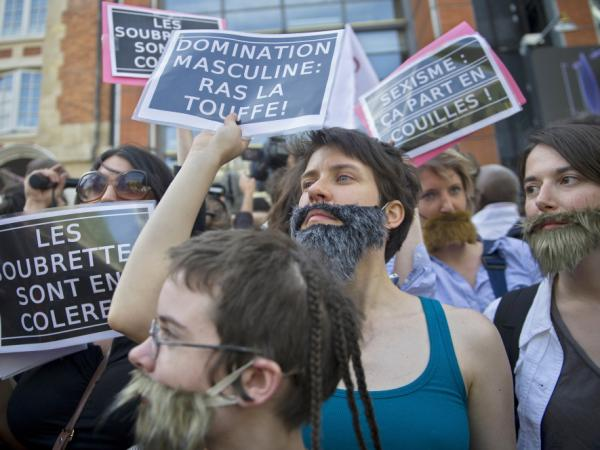 Women, mostly members of feminist groups, wear fake mustaches and beards and hold anti-sexist placards as they stage a demonstration in Paris against the political and media reaction to the sexual assault allegations against former IMF chief Dominique Strauss-Kahn, May 22.