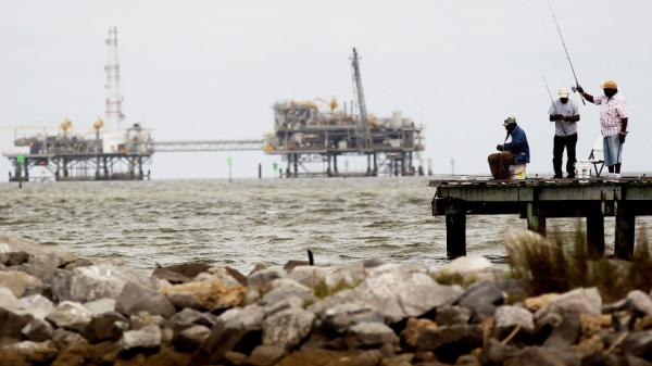 <p>Men fish off a pier at a jetty in Dauphin Island, Ala., with oil rigs in the background. The U.S. government is changing how it regulates drilling platforms.</p>