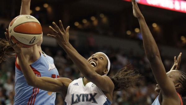<p>Minnesota Lynx guard Candice Wiggins, center, goes up for a shot against Atlanta Dream center Alison Bales, left, and forward Sancho Lyttle, right, in the second half of Game 1 of the WNBA finals basketball series on Sunday.</p>