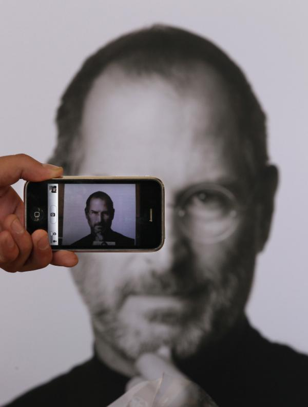<p>A photographer uses his iPhone to take a picture of a tribute to Apple co-founder Steve Jobs in front of an Apple store in London. Jobs, 56, died Wednesday after a long battle with pancreatic cancer.</p>