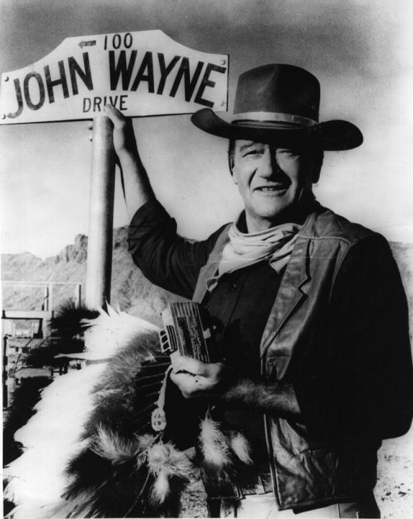"<p>American actor John Wayne stands by the street sign honoring his name in Prescott, Ariz. The film star ""was one of the defining Americans of the 20th century,"" says critic John Powers.</p>"