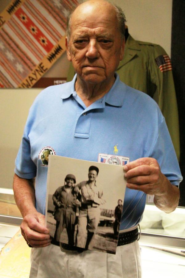 <p>Bill Atkins, 80, holds a blurry photo of himself at age 19 with John Wayne during the filming of <em>Flying Leathernecks</em>. Atkins came from Bowie, Md., to view the auction. </p>