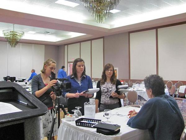 From left to right, student filmmakers Elizabeth Herzfeldt-Kamprath, Hailey Rile and Katie Scaff interview the keynote speaker at a compassion fatigue conference in Ontario, Canada. Courtesy of PLU
