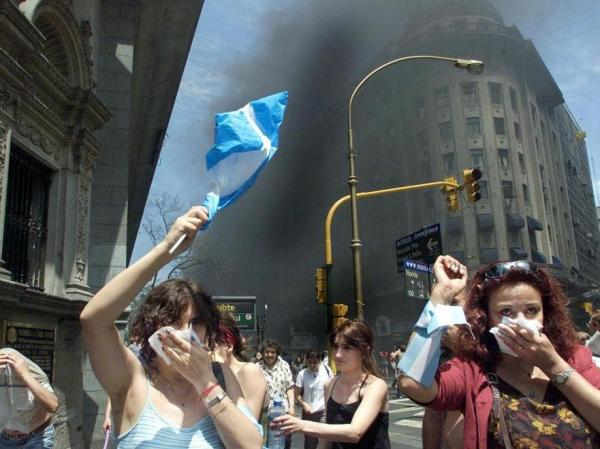 <p>Protesters in Argentina in 2001 wave national flags as they walk through tear gas and smoke from burning street fires set by demonstrators during the country's financial crisis.</p>