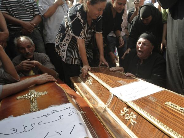 <p>Egyptians grieve over the coffins of Coptic Christians killed during Sunday's clashes with Egyptian security forces, before beginning a funeral procession from the Coptic Hospital in Cairo.</p>