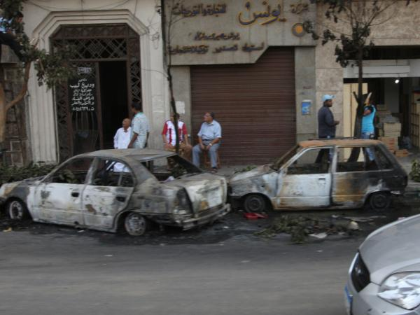 <p>Torched vehicles and damaged trees line are seen in Cairo on the morning after clashes between Coptic Christians and Egyptian security forces left more than two dozen people dead.</p>